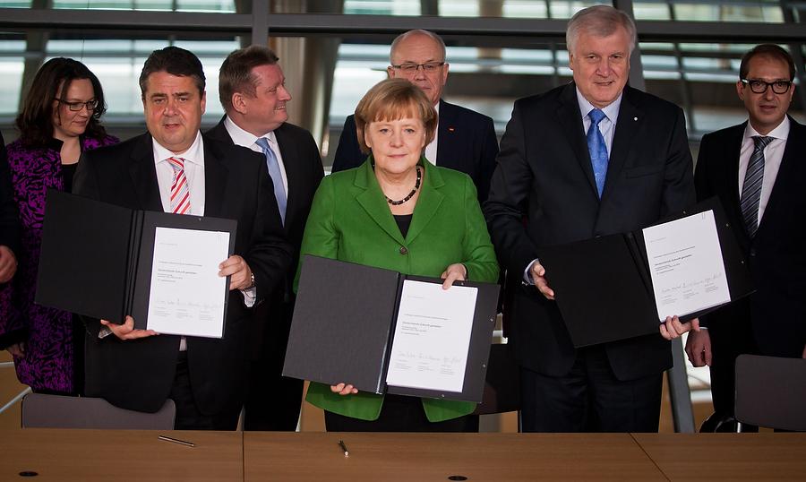 Sigmar Garbiel (l.), Angela Merkel und Horst Seehofer (r.) präsentieren am Mittwoch den unterschriebenen Koalitionsvertrag auf der Fraktionsebene im Reichstag.